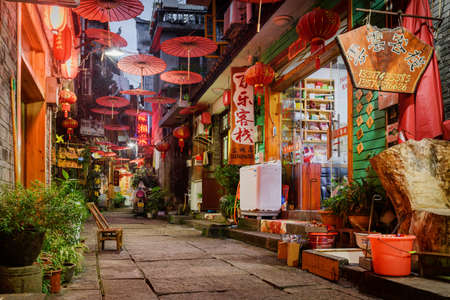 Fenghuang, China - September 22, 2017: Wonderful view of scenic narrow street decorated with traditional oriental Chinese red umbrellas in Phoenix Ancient Town (Fenghuang County) at evening.
