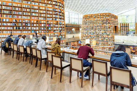 Seoul, South Korea - October 14, 2017: Visitors at the Starfield Library reading area. Huge bookshelves are visible in background. The public library is a popular attraction of Seoul.