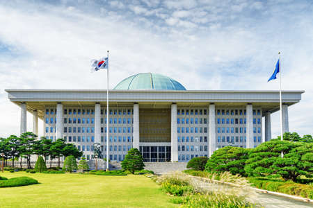 The main view of the National Assembly Proceeding Hall at Seoul in the Republic of Korea. The building of the South Korean national government. The flag of the South Korea on the sky background. Editorial