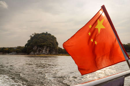 The flag of the People's Republic of China (the Five-star Red Flag) fluttering on boat sailing on the Li River (Lijiang River) in Guilin at sunset. The Elephant Trunk Hill is visible in background.