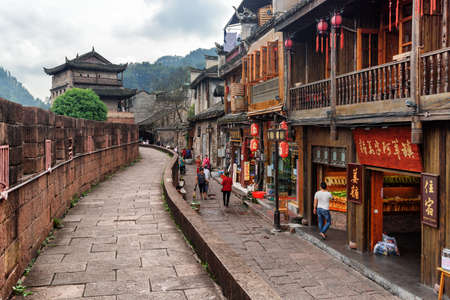 Fenghuang, China - September 22, 2017: View of town wall and street with souvenir shops and restaurants in Phoenix Ancient Town. East Gate Tower of Xiangxi is visible on wooded mountains background.