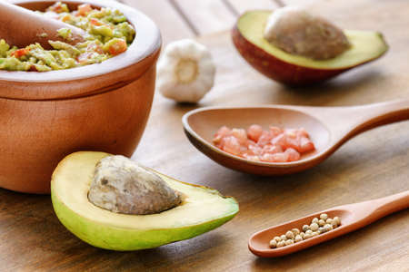 Closeup view of ripe avocado and fresh homemade Guacamole in wooden mortar with pestle (molcajete). Traditional Mexican sauce. Healthy vegetarian eco food. Stock Photo