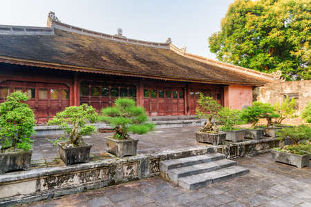 Amazing red building at the Tu Duc Royal Tomb in Hue, Vietnam. Green Bonsai trees growing beside the building. Hue is a popular tourist destination of Asia.