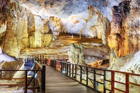 Wooden walkway among amazing stalactites and stalagmites inside Paradise Cave (Thien Duong Cave) at Phong Nha-Ke Bang National Park in Vietnam. Paradise Cave is a popular tourist attraction of Asia. Stock Photo