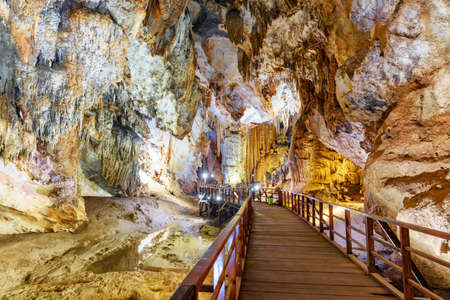 Scenic wooden winding walkway among beautiful stalactites inside Paradise Cave (Thien Duong Cave) at Phong Nha-Ke Bang National Park of Vietnam. Paradise Cave is a popular tourist attraction of Asia. Фото со стока - 102203462
