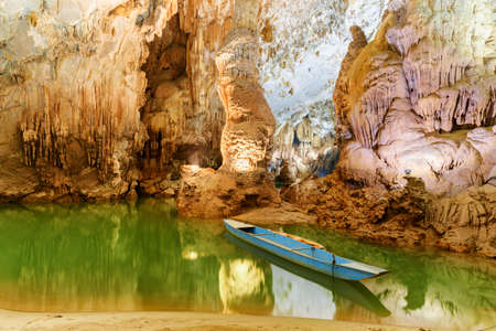 Old blue boat parked inside Phong Nha Cave at Phong Nha-Ke Bang National Park in Vietnam. Underground part of the Son River among beautiful stalactites and stalagmites of the wet cave.