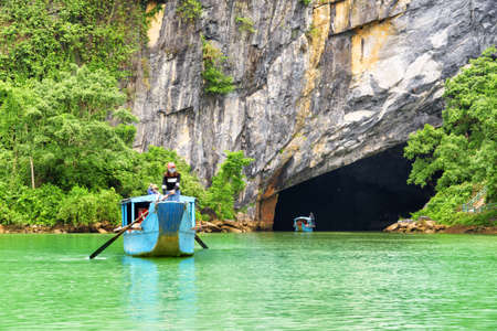 Entry to Phong Nha Cave by the Son River at Phong Nha-Ke Bang National Park in Vietnam. Tourists traveling along the river by boats. Phong Nha Cave is a popular tourist attraction of Asia.