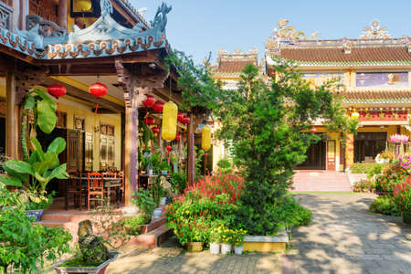 Hoi An (Hoian), Vietnam - April 11, 2018: Amazing view of cafe decorated with traditional yellow and red silk lanterns in beautiful garden of Phap Bao Temple in Hoi An Ancient Town.
