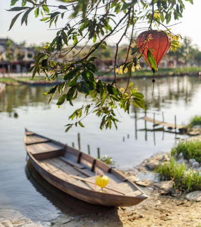 Scenic view of green tree branches decorated with traditional red lantern in Hoi An Ancient Town (Hoian), Vietnam. Wooden boat parked on bank of the Thu Bon River. Focus on the foliage. Stock Photo