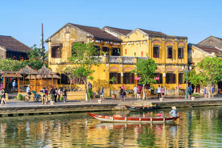 Hoi An (Hoian), Vietnam - April 11, 2018: View of traditional yellow building of Hoi An Ancient Town. Tourists walking along embankment of the Thu Bon River. Vietnamese woman in bamboo hat on boat.