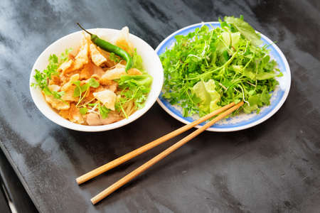 Bowl of Cao Lau in street cafe at Hoi An (Hoian), Quang Nam Province of central Vietnam. Cao Lau is a regional Vietnamese dish made with noodles, pork and local greens. Cao Lau is found only in Hoi An