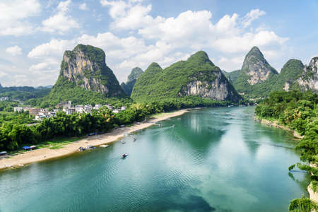 Scenic view of the Li River (Lijiang River) with azure water among beautiful karst mountains at Yangshuo County of Guilin, China. Wonderful green hills on blue sky background. Amazing summer landscape
