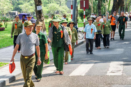 Hue, Vietnam - April 4, 2018: Group of Vietnamese veterans walking along road to the Imperial City with the Purple Forbidden City within the Citadel. Hue is a popular tourist destination of Asia. Editorial