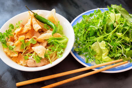 Cao Lau in street cafe of Hoi An (Hoian) at Quang Nam Province of central Vietnam. Cao Lau is a regional Vietnamese dish made with noodles, pork and local greens. Cao Lau is found only in Hoi An. Stock Photo
