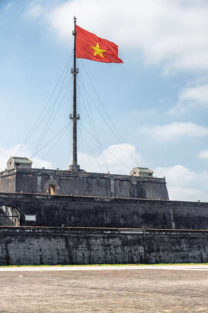 Beautiful view of the flag of Vietnam (red flag with a gold star) fluttering over a tower of the Citadel on blue sky background in Hue, Vietnam. Within the Citadel is the Imperial City.