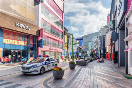 Busan, South Korea - October 7, 2017: Gwangbokro Cultural and Fashion Street in morning. Police car driving down the street. Gwangbokro is a popular tourist destination of Asia.