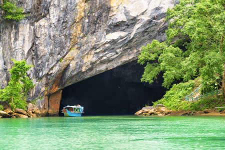 Scenic entry to Phong Nha Cave by the Son River at Phong Nha-Ke Bang National Park in Vietnam. Phong Nha Cave is a popular tourist attraction of Asia.