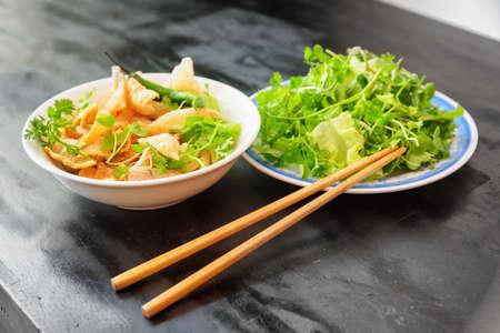 Cao Lau sur table de café de rue à Hoi An (Hoian) dans la province de Quang Nam au Vietnam. Cao Lau est un plat vietnamien régional à base de nouilles, de porc et de légumes verts locaux. Cao Lau se trouve uniquement à Hoi An.