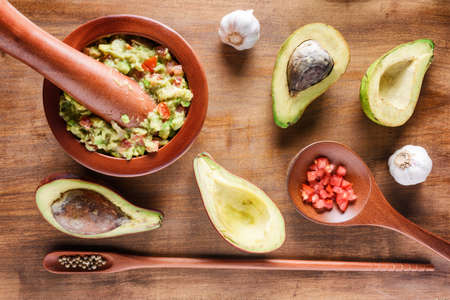 Top view of fresh homemade Guacamole in wooden mortar with pestle (molcajete). Traditional Mexican sauce from ripe avocados on wooden table. Healthy vegetarian eco food. Stock Photo