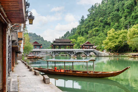 Parked wooden tourist boat on the Tuojiang River and scenic bridge among green woods in Phoenix Ancient Town (Fenghuang County), China. Fenghuang is a popular tourist destination of Asia.