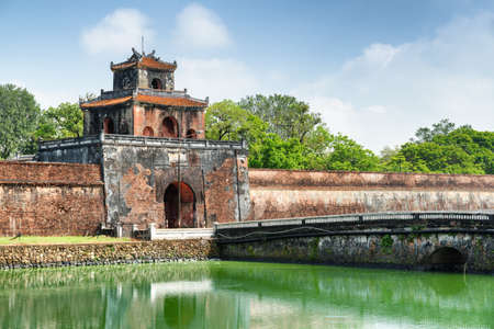 Scenic view of the Ngan Gate in fortress wall of the Citadel and a bridge over moat surrounding the Imperial City with the Purple Forbidden City, Hue, Vietnam. Hue is a popular tourist destination.
