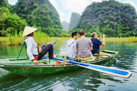 Tourists traveling in small boat along the Ngo Dong River and taking picture of the Tam Coc, Ninh Binh, Vietnam. Rower using her feet to propel oars. Landscape formed by karst towers and rice fields. Editorial