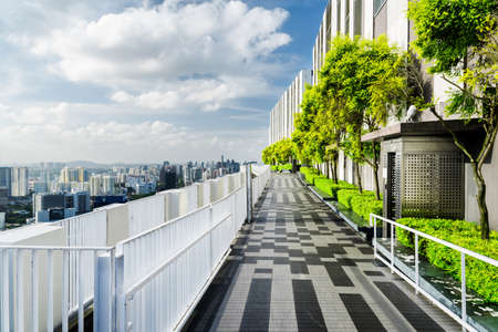 Beautiful rooftop garden. Amazing outside terrace with park and scenic city view. Modern benches under green trees along walkway. Urban eco design and mini-ecosystem. Landscaping in Singapore.