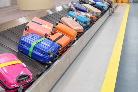 Bright colorful suitcases and bags on luggage conveyor belt at arrival area of passenger terminal in airport. Baggage carousel. Stockfoto