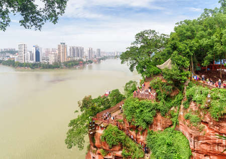 Leshan, China - September 28, 2017: Beautiful view of the city and the confluence of the Min River (Min Jiang) and Dadu River. Asian tourists going down stairs to the Leshan Giant Buddha.
