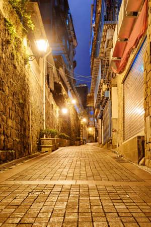 Amazing night view of deserted narrow street at old town of Macau. Historic Centre of Macao is a popular tourist attraction of Asia.