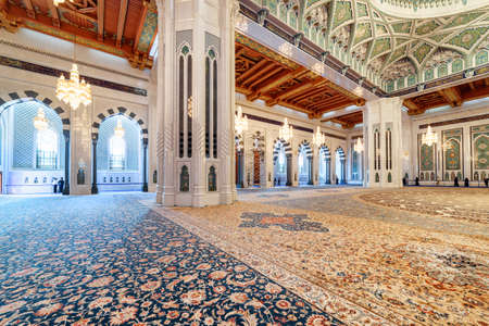 Muscat, Oman - 17 October, 2018: Beautiful carpet in the main prayer hall of the Sultan Qaboos Grand Mosque. Wonderful interior of the Muslim place. Amazing Islamic architecture and decoration. Éditoriale