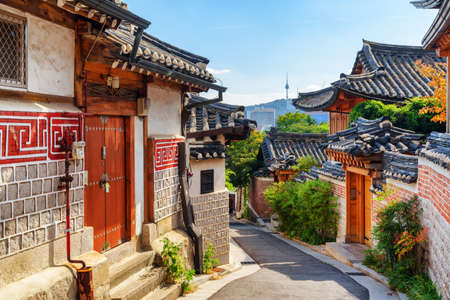 Awesome view of cozy old narrow street and traditional Korean houses of Bukchon Hanok Village in Seoul, South Korea. Seoul Tower on Namsan Mountain is visible on blue sky background. Scenic cityscape. Banque d'images