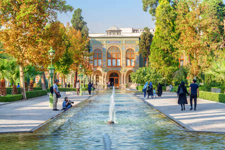 Tehran, Iran - 19 October, 2018: Tourists and residents enjoying views of scenic fountains and walking along garden of the Golestan Palace. Wonderful traditional Persian exterior.
