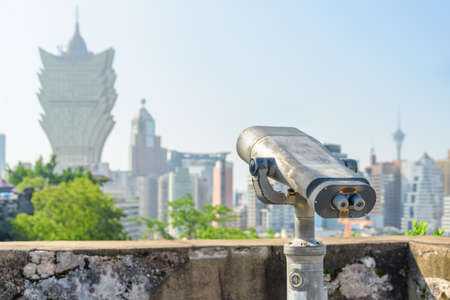 Vintage tower viewer at observation deck in Macau. Coin-operated binoculars placed in a popular tourist destination of Asia. Amazing Macau skyline is visible in background.