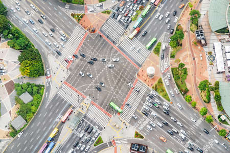 Scenic aerial view of road intersection at downtown of Seoul in South Korea. Cars and colorful buses on streets. Day traffic. Seoul is a popular tourist destination of Asia.