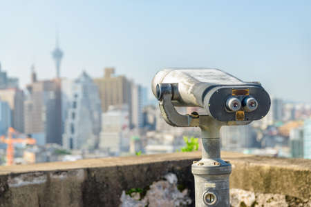 Threadbare tower viewer at observation deck in Macau. Coin-operated binoculars placed in a popular tourist destination of Asia. Amazing Macau skyline is visible in background.