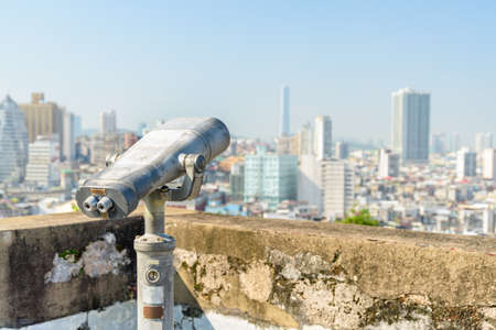 Shabby tower viewer at observation deck in Macau. Coin-operated binoculars placed in a popular tourist destination of Asia. Amazing Macau skyline is visible in background.