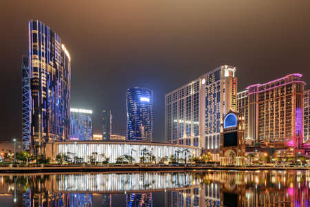 Beautiful night view of modern buildings in Cotai of Macau. Colorful city lights reflected in water. Wonderful cityscape. Cotai is a new gambling and tourism area with casinos and shopping malls.
