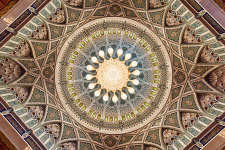 Muscat, Oman - 17 October, 2018: Beautiful view of ceiling of the main prayer hall in the Sultan Qaboos Grand Mosque. Wonderful details of amazing interior of the Muslim place.