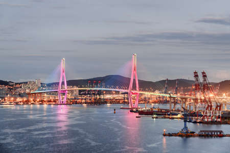 Colorful evening view of Busan Harbor Bridge and the Port of Busan in South Korea.