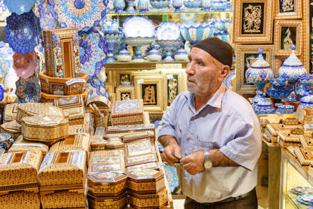 Isfahan, Iran - 24 October, 2018: Elderly Iranian seller at gift shop in the Grand Bazaar (Qeysarie Bazaar). Beautiful Persian wooden and colorful ceramic souvenirs. Traditional patterns and ornaments Standard-Bild - 121384821