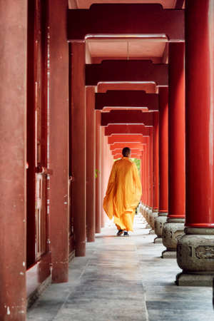 Chinese Buddhist monk walking along red wooden corridor of a monastery to a temple. Monk wearing yellow robe.
