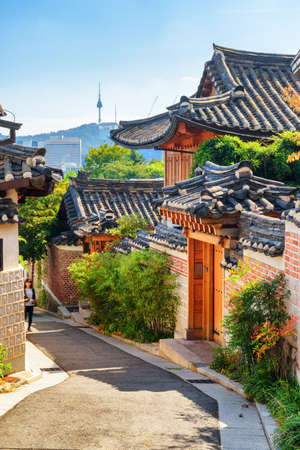 Scenic old narrow street and traditional Korean houses of Bukchon Hanok Village in Seoul, South Korea. Seoul Tower on Namsan Mountain is visible on blue sky background. Beautiful cityscape.