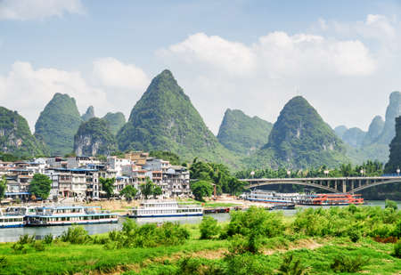 Amazing view of Yangshuo Town, beautiful bridge and wonderful karst mountains on blue sky background. Scenic sunny landscape. Tourist boats are visible on the Li River (Lijiang River), Guilin, China. Zdjęcie Seryjne