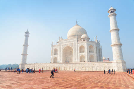 Gorgeous view of the Taj Mahal on blue sky background in Agra, India. Visitors walking to the white marble mausoleum. The Taj Mahal is a popular tourist attraction of South Asia. Mughal architecture. Stok Fotoğraf
