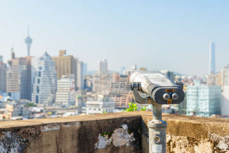 Old shabby tower viewer at observation deck in Macau. Coin-operated binoculars placed in a popular tourist destination of Asia. Amazing Macau skyline is visible in background.