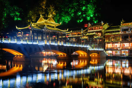 Amazing night view of colorful bridge over the Tuojiang River (Tuo Jiang River) in Phoenix Ancient Town (Fenghuang County), China. Fenghuang is a popular tourist destination of Asia. Zdjęcie Seryjne