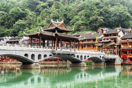 Amazing view of scenic bridge over the Tuojiang River (Tuo Jiang River) among green woods in Phoenix Ancient Town (Fenghuang County), China. Fenghuang is a popular tourist destination of Asia. Zdjęcie Seryjne - 125871337
