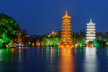Beautiful night view of the Sun and Moon Twin Pagodas at Shanhu Lake (Fir Lake). Gold and Silver Pagodas illuminated at downtown of Guilin, China. Guilin is a popular tourist destination of Asia. Zdjęcie Seryjne - 125871338