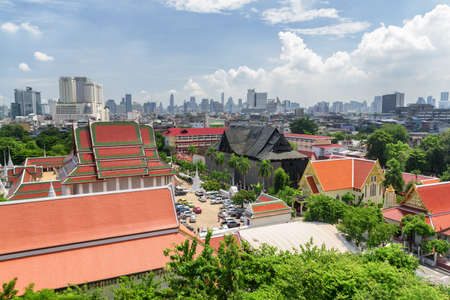 Beautiful cityscape in Bangkok, Thailand. Aerial view of traditional orange roofs of Buddhist temple. Skyscrapers and other modern buildings are visible on blue sky background. Amazing Bangkok skyline Zdjęcie Seryjne - 125871341